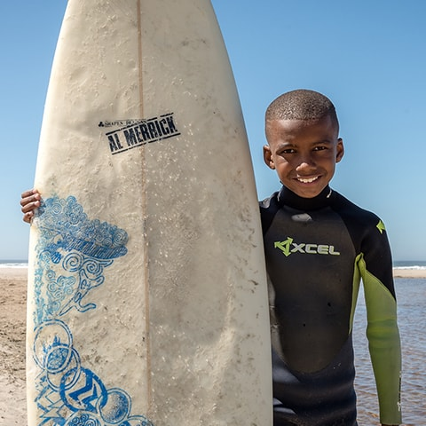 Smiling Smile Surfer holding a surf board, who is the son of our Sumner dentist, Dr. Jared Lothyan