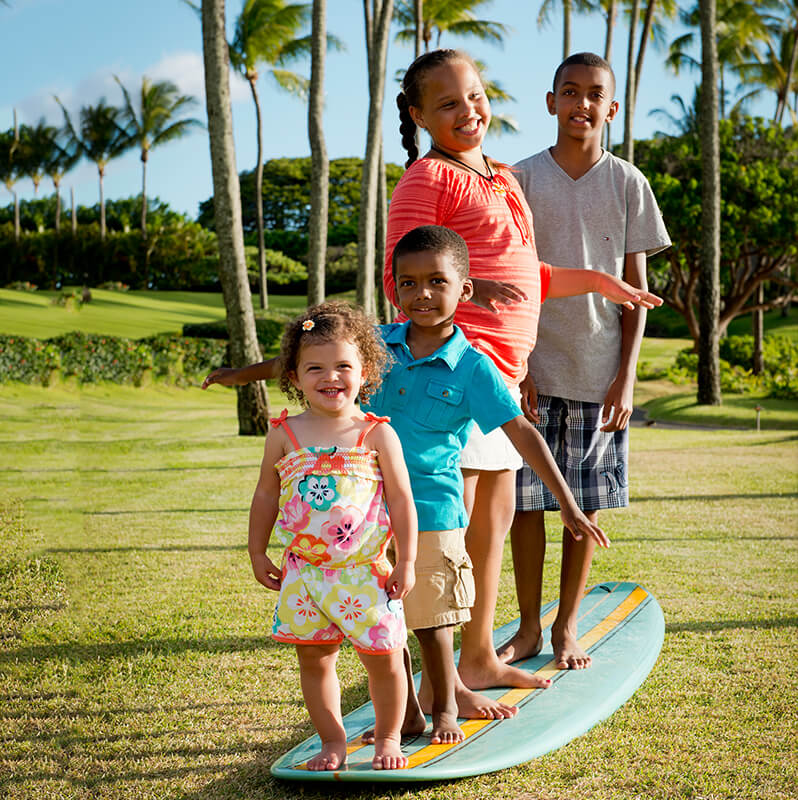Little children having fun outside pretending to surf on a surfboard