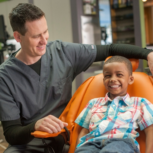 Smiling young boy in orange dental chair next to watchful dentist.