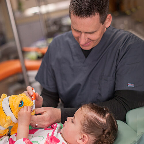 Dentist showing a little girl laying in dental chair how to brush her teeth using a stuffed animal.